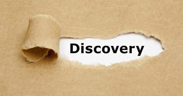 The word Discovery appearing behind torn brown paper.